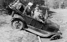 Humorous black and white image of vintage car stuck in ditch.